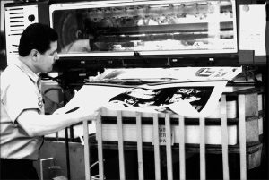 pressman pulling printed sheets for book, The Art of Making Opera