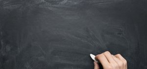 empty blackboard and hand with chalk