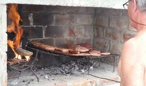 man tending grilled meats on a parrilla in Uruguay