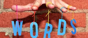 cut-out letters spell WORDS hung from strings like marionettes