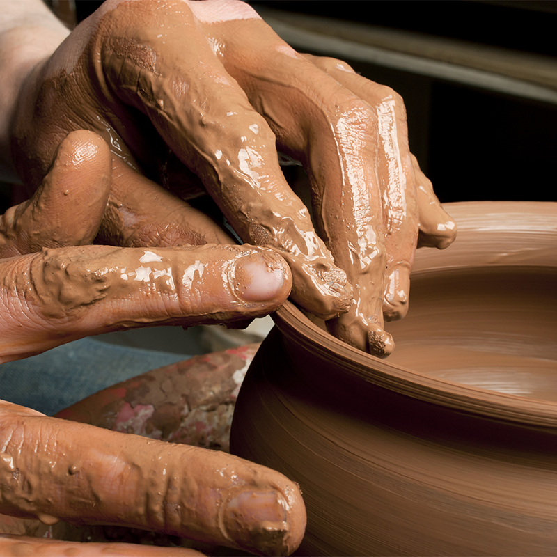 artists and craft in the studio - hands shaping a clay pot