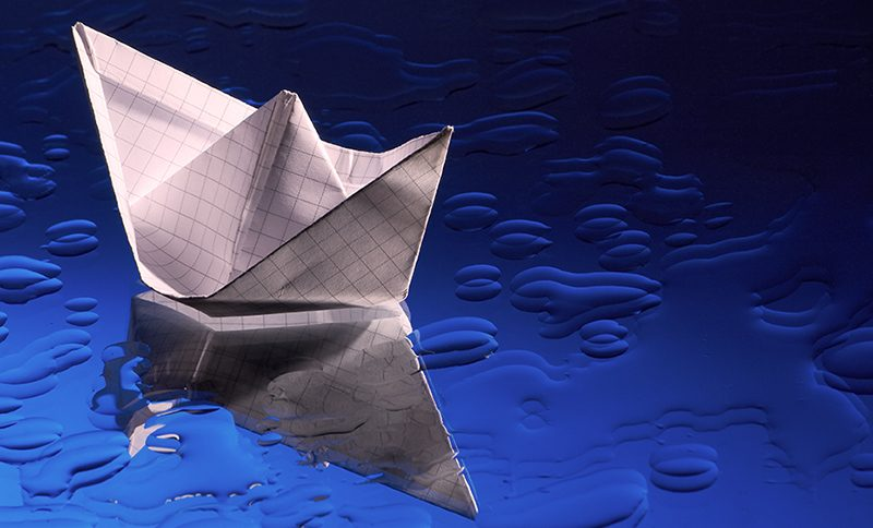 small boat on an ocean - paper boat on mirror