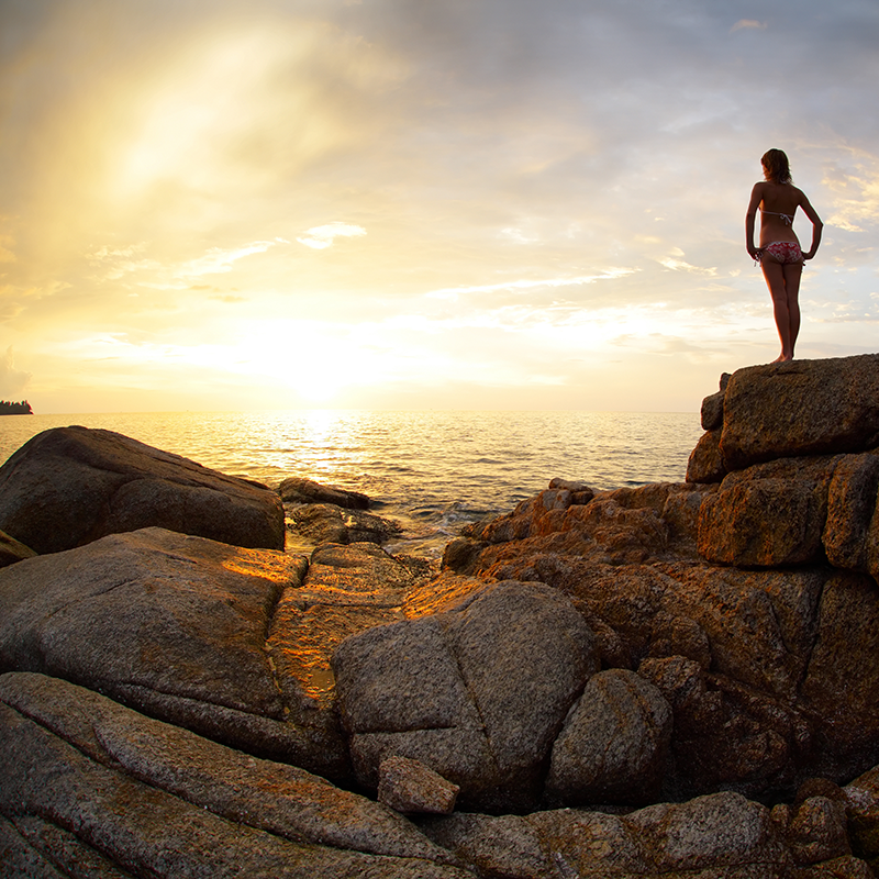 far and familiar, a woman stands on a rocky beach gazing across the ocean towards the horizon, dreaming of travel